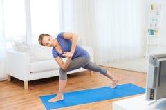 Woman making yoga low angle lunge pose on mat Stock Image