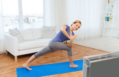 Woman making yoga low angle lunge pose on mat. Fitness, sport, people and healthy lifestyle concept - woman making yoga low angle lunge pose on mat and watching Stock Photos