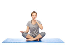 Woman making yoga meditation in lotus pose on mat Royalty Free Stock Photography