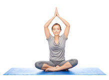 Woman making yoga meditation in lotus pose on mat Stock Photography