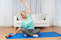 Woman making yoga meditation in lotus pose on mat Royalty Free Stock Image