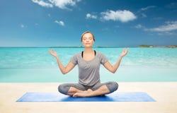 Woman making yoga meditation in lotus pose on mat Stock Images