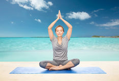 Woman making yoga meditation in lotus pose on mat Stock Images