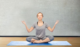 Woman making yoga meditation in lotus pose on mat Royalty Free Stock Photo