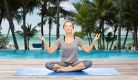 Woman making yoga meditation in lotus pose on mat Stock Photo