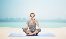 Woman making yoga meditation in lotus pose on mat Royalty Free Stock Photos