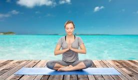 Woman making yoga meditation in lotus pose on mat Royalty Free Stock Images