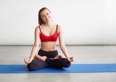 Woman making yoga meditation in lotus pose on mat Stock Image
