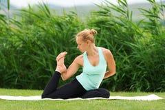 Woman making yoga one legged king pigeon Stock Photos