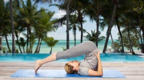 Woman making yoga in plow pose on mat Royalty Free Stock Image