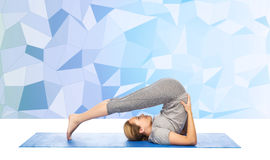 Woman making yoga in plow pose on mat Royalty Free Stock Photography