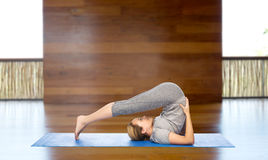 Woman making yoga in plow pose on mat Stock Photo