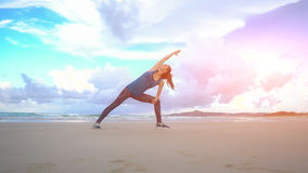 Woman is making yoga pose on beach in Vietnam. Sea or ocean happy female relaxation. Water and waves. Hands and blue sky Stock Photos