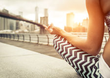 Woman making yoga position in New york city. Woman making yoga position in New york city at sunset time. Brooklyn bridge and new york skyline in the background royalty free stock photos