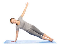 Woman making yoga in side plank pose on mat Stock Images