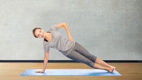Woman making yoga in side plank pose on mat Stock Image