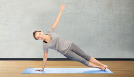 Woman making yoga in side plank pose on mat Royalty Free Stock Images