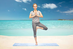 Woman making yoga in tree pose on beach Royalty Free Stock Photo