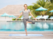 Woman making yoga in tree pose on mat Stock Photo