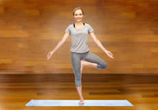 Woman making yoga in tree pose on mat Royalty Free Stock Image