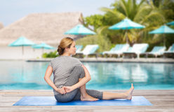 Woman making yoga in twist pose on mat. Fitness, sport, people and healthy lifestyle concept - woman making yoga in twist pose on mat over beach and swimming Stock Photo