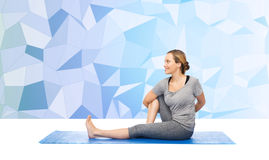 Woman making yoga in twist pose on mat Stock Photography