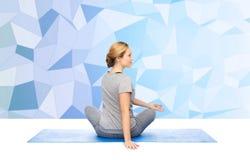 Woman making yoga in twist pose on mat Royalty Free Stock Image