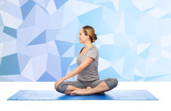 Woman making yoga in twist pose on mat Stock Images