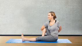 Woman making yoga in twist pose on mat. Fitness, sport, people and healthy lifestyle concept - woman making yoga in twist pose on mat over room or gym background Royalty Free Stock Images