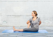 Woman making yoga in twist pose on mat Royalty Free Stock Images
