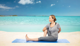 Woman making yoga in twist pose on mat over beach. Fitness, sport, people and healthy lifestyle concept - woman making yoga in twist pose on mat over sea and sky Stock Photography