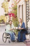 Smiling Woman with Man in Wheelchair Outdoors. Woman and male friend in wheelchair having coffee Stock Image