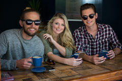 Woman with male friends wearing sunglasses in coffee shop. Portrait of woman with male friends wearing sunglasses in coffee shop Royalty Free Stock Photos