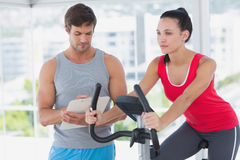 Woman with male instructor working out at spinning class Royalty Free Stock Photography