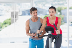 Woman with male instructor working out at spinning class Royalty Free Stock Photo
