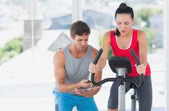 Woman with male instructor working out at spinning class Stock Images