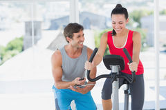 Woman with male instructor working out at spinning class Royalty Free Stock Images