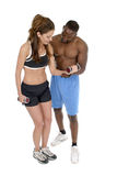 Woman With Male Personal Trainer 1. Woman in fitness workout clothing is getting help from a male personal trainer in using hand weights. Isolated shot on white Stock Photography