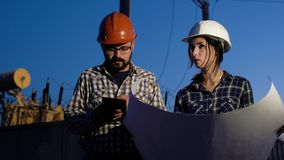 Woman in the male profession. Two engineers make calculations on a big piece of paper, looking around and checking