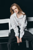 Woman in male shirt sitting on chairs. On black background, studio shot Stock Images