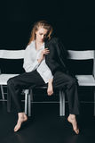 Woman in male shirt sitting on chairs. On black background, studio shot Stock Photo