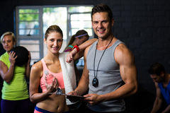 Woman with male trainer in fitness studio. Portrait of smiling women with male trainer in fitness studio Royalty Free Stock Images