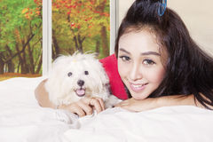 Woman with maltese dog in autumn season. Young woman lying on the bed with an embracing cute maltese dog in autumn season Stock Images