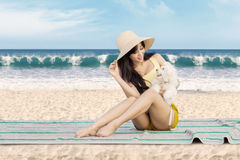 Woman with maltese dog at beach. Happy young woman sitting on the mat at beach while holding a maltese dog and smiling Stock Image