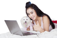 Woman with maltese dog showing thumb up. Image of attractive young woman with maltese dog and laptop while showing thumb up at the camera on the bed Stock Photos