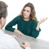 Woman and man in argument at a table Stock Photos