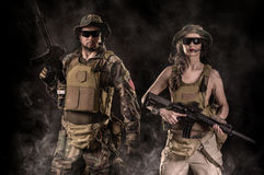 Woman and a man with an assault rifle. Sexy women and a men with an assault rifle on a black background Royalty Free Stock Image