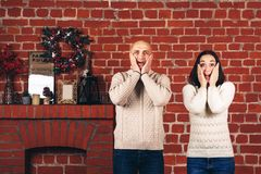 A woman and a man on the background of a brick wall show emotions: wow, shock, incredible, surprise. A women and a men on the background of a brick wall show royalty free stock photos