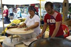 Woman and man bake Turkish bread. Kemer, Turkey. A woman and  a man bake traditional Turkish flat bread (Borek) on the market in special oven. Kemer, Turkey Stock Photos