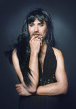 Woman man with a beard in a dress. Guy in a wig with a beard, wearing a dress seduces Royalty Free Stock Photography